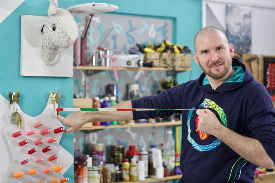 Jan Leśniak w pracowni Majsterek z projektem półki na nici w kształcie sukienki.